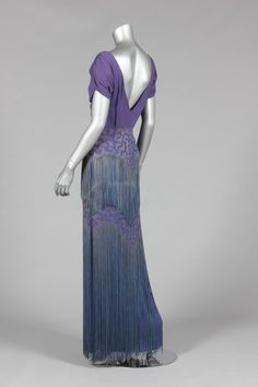 An early Mainbocher purple satin-backed crêpe evening gown, 1930s, labelled '12 Avenue George V, Paris', with ruched bodice, interesting sleeve details, embroidered and fringed in silver-blue cord, bust 97cm, 38in