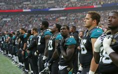 Jacksonville Jaguars players observe the US national anthem before an NFL football game against Indianapolis Colts at Wembley stadium in London, Sunday Oct. 2, 2016.