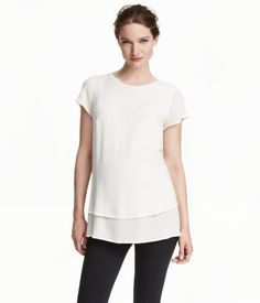 MAMA Creped Blouse - White. Short-sleeved blouse in woven, crêped fabric layered over a slightly longer lining. Opening at back of neck with button.