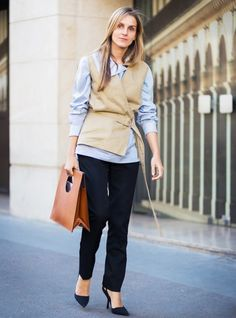 Layer a blue button-down shirt underneath your vest and polish off your look with black pumps