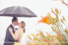 Such an artistic engagement photo!  Love the focus on the flowers, and the couple blurry in the background.  Plus, the raindrops and the umbrella are so magical looking!  From a photo shoot on the Seacoast in NH.