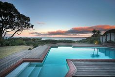 Stunning swimming pool, that overlooks the ocean, beautiful blue and orange sky behind. From 4 bedroom home @ Red Bluff Rise, Campbells Bay.