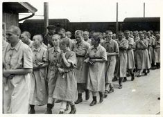 """Women fit for work after the delousing process. The disinfection of those not selected for the gas chambers, and the shaving of their heads, was all part of the """"registration""""  process at the camp. After they finished, they were given the prison uniforms seen in the picture."""
