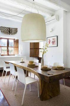 magnifique table dans la salle à manger en bois brut, lustre en tissu beige, chaises blanches