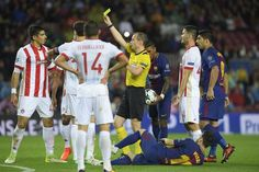 Olympiacos' Greek defender Dimitris Nikolaou (L) receives a yellow card as Barcelona's Argentinian forward Lionel Messi (bottom) lies on the field during the UEFA Champions League group D football match FC Barcelona vs Olympiacos FC at the Camp Nou stadium in Barcelona on Ocotber 18, 2017. / AFP PHOTO / LLUIS GENE