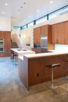 Modern kitchen of custom home in Denver, Colorado. Features: grain-matched custom walnut cabinets, Caesarstone Pure White countertops, waterfall countertop, Jenn-Air appliances, Miele coffee system, clerestory windows, and exposed concrete floor. Home designed and built by West Standard.