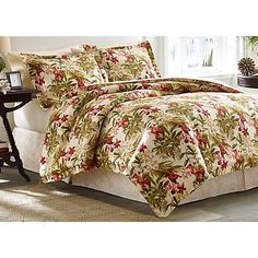 Tommy Bahama's Daintree Tropics comforter features a leafy greens mix with coral, gold and white orchids on a warm ivory ground, reversing to a tonal iv...