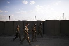 Paratroopers from the 3rd Battalion (Airborne), 509th Infantry of the 4th Brigade Combat Team, 25th Infantry Division walk along a wall of hesco barriers at FOB Gardez in Afghanistan's Paktiya Province