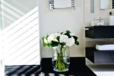 A simple vase of white hydrangea heads add the finishing touch to a bathroom. http://www.kellyhoppen.com/shop-by-type/books-and-pictures/kelly-hoppen-design-masterclass-how-to-achieve-the-home-of-your-dreams
