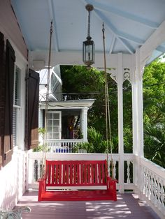Red porch swing at The Popular House B&B, Key West, Florida