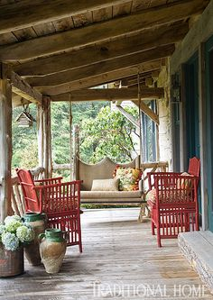Rattan chairs and a custom swing covered in burlap offer easy seating on the front porch, which looks to the lake. - Photo: Jenifer Jordan / Design: Charles Faudree
