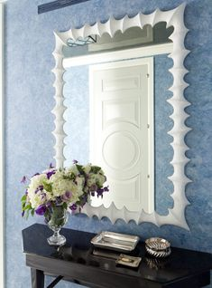 Foyer vignette with white spiky mirror, glossy black console table and blue paint color.