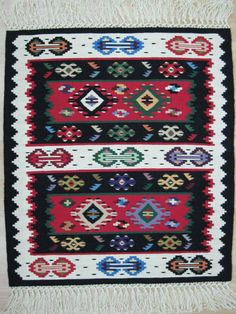 """Кувери"", Пиротски ћилим Pirotski ćilim, kreacija Zadruge Damsko srce, Pirot. Pirot kilim is a unique and highly regarded brand of flat tapestry-woven carpets or rugs, made of pure sheep's wool ( from Stara Planina, southeastern Serbia), dyed with natural colours and long enduring. Has 28 weave lines in 1cm and both sides of the rug can be used. Its patterns and ornaments are unique: 96 of them are geographically protected. Pirot kilim is made exclusively in Pirot, Serbia."