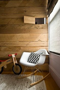 Rustic nursery features plank walls with secret doors with view to another room alongside an Eames Molded Plastic Chair accented with a black and white chevron pillow and a Diggin Skuut Balance Bike atop a natural pebbled rug. Modern Kids Furniture, Home Furniture, Kids Lounge Chair, Decoracion Vintage Chic, Baby Barn, Plank Walls, Rustic Nursery, Inspired Homes, Home Fashion
