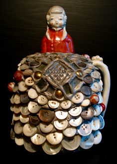 A button jug topped with a frozen Charlotte. Interesting that the buttons are angled, not flat as usually seen in this sort of art.