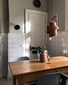 Küche - Geschwungene Lampe aus Leder/Holztisch/graue Stühle/weiße Fliesen
