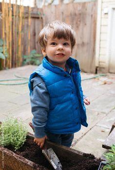 Boy looks at camera mid planting.