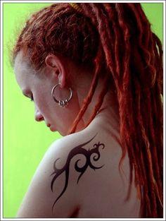 Piccolo tatuaggio tribale tra braccio e scapola