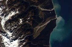 Silt-laden glacier waters billow blue into the sea at the south of New Zealand.