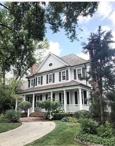 Beautiful white house with black shutters and wraparound front porch
