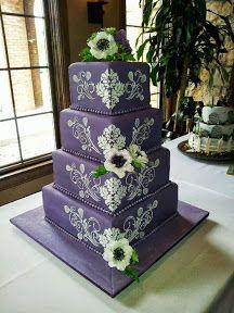 Un pastel de cuatro pisos color violeta con detalles de flores en blanco Purple Wedding Cake