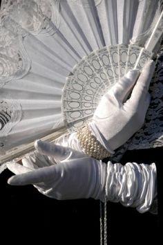 white gloved hands holding white fan