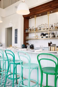 white bar interior with jade green cafe stools, emerald green, mint green, pantone arcadia