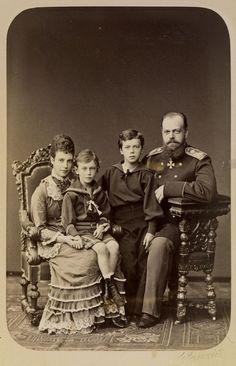 Czarevich Alexandre e Czarina Maria Feodorovna, mais tarde Imperatriz da Rússia, com seus dois filhos mais velhos grão-duque Nicolau Alexandrovich, mais tarde Nicholas II e Grão-Duque George Alexandrovich. Czarevich Alexandre está sentado em uma cadeira de madeira ornamentado para a direita, vestindo uniforme militar. Czarina Maria Feodorovna está sentada em uma cadeira semelhante à esquerda com o Grão-duque George sentado em seu joelho. Grão-duque Nicholas está de pé entre eles.1878.
