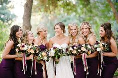 love the ribbon hanging from their deep purple bouquets