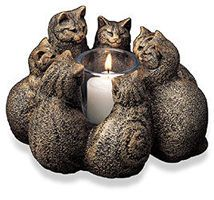 "Circle of Cats Candleholder Seven feline guardians gather to observe the flickering flame in the center of their circle. Each cat is imbued with its own alluring personality. Look for the Celtic spiral and Tree of Life on the cats backs, then light a candle and let them do their magic. Made of cast stone; includes candle. For indoor use only. Approximately 4 1/2"" tall. Made in USA. Gift wrap and rush delivery not available.  $88.00"