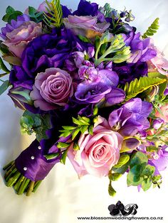 """Bride's bouquet of purple lisianthus, purple stock, purple delphinium, purple freesia, dusky purple and coffee """"old dutch"""" roses, with touches of ladder fern, eucalyptus and berries, bound in deep purple satin.    Visit us here: www.blossomweddingflowers.co.nz Friend us here: www.facebook.com/pages/Auckland/Blossom-Wedding-Flowers/2..."""