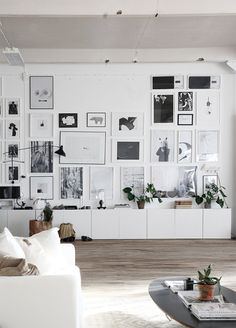 great gallery wall in crisp white living room with lovely wood floors