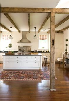 rustic kitchen - beams, cream cabinets, no upper cabinets