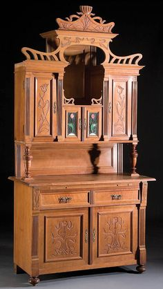 AUSTRIAN ART NOUVEAU WALNUT AND STAINED GLASS SIDE CABINET late 19th century with stylized floral decoration on intaglio carved panels below a stylized reticulated top.