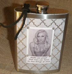 """Saying on Flask - """"Boobs are proof that men can focus on two things at once"""" - Item #UT-105 - Price before discount $33.99.  Background - gray, silver metallic Embellishment - black suede tie, clear rhinestones Flask is handmade using an 8 ounce stainless steel flask. Has a decorative paper background and image printed on high quality white paper. Is embellished with leather, rhinestones, studs or beads depending on the style of the flask. Comes with a stainless steel funnel to fill your…"""