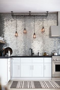 Such a cool kitchen … stainless metal mosaic tiles, aged bronze cage pendant lights, an adjoining...