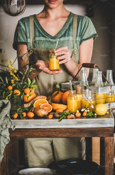 Young woman holding bottle of fruit vitamin immune boosting drink by sonyakamoz. Young woman in apron holding homemade fresh turmeric, ginger, citrus . Fresh Turmeric, Coffee Images, Drink Photo, Citrus Juice, Young Women, Herbalism, Vitamins, Clean Eating, Food And Drink