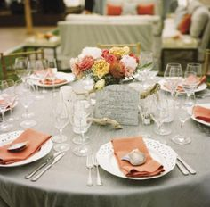 MIXED MATCH: Set against a muted Tuscany linen tablecloth, coral napkins and blooms gave the dining tables spring appeal; white eyelet plates from Snyder Event Rentals and white blown glass votives added crisp contrast.