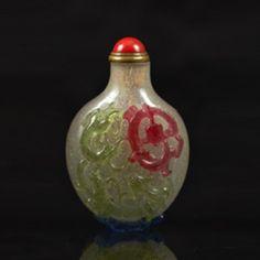 CHINE - XVIIIe siècle  Flacon tabatière en verre overlay rouge, vert, jaune et bleu sur fond bullé translucide, à décor de qilong mouvementés, l'un formant pied.  H.6 cm