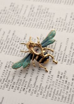 This weird little eye candy piece is painted on a teeny tiny 1/4 inch canvas set into a vintage 3/4 inch cameo frame fixed onto a sweet hand painted, enameled honey bee pin/brooch setting.