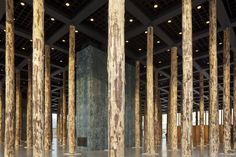 Using 144 imposing tree trunks, British architect David Chipperfield transforms the open glass hall of the Neue Nationalgalerie into a densely filled hall of columns for a three-month period. The installation Sticks and Stones engages with the architecture of the museum, designed by Ludwig Mies Van der Rohe, and simultaneously serves as a prologue to the upcoming overall renovation of the museum that David Chipperfield Architects will undertake starting in 2015. Photo by David Von Becker.