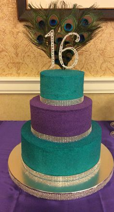 Peacock themed sweet sixteen! This three tiered cake is covered entirely in sanding sugar in purple and teal. The trim is ribbon made to look like rhinestones. The flavors included chocolate chip pound cake, vanilla almond, and chocolate with cookies and cream filling.