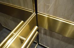 """Two 1-1/2"""" [38mm] dia Brushed and Lacquered Brass Tubular Handrails Anchored to a Brushed Brass Support Band Provide Protection for the Bronzed Mirrors in this Elevator Interior by Premier Elevator."""