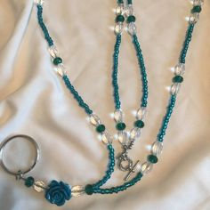 Beaded Lanyard: Crystal Handmade beaded lanyard. Greenish blue and clear beads, and a turquoise rose for a focal point. This is such a beautiful lanyard. Make your keys looks fabulous! Jewelry Necklaces
