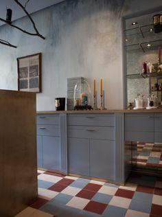 Modern Kitchen inspiration: blue-grey, brass toe kick , mirror backsplash and cement floor tiles.