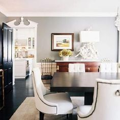 Beautiful dining room design with gray walls paint color, antique buffet, marble top gold console table, glossy black door, modern rectangular dining table and Baker white tufted dining chairs with nailhead trim. Gray Painted Walls, Grey Walls, Grey Paint, Veranda Interiors, Tufted Dining Chairs, Beautiful Dining Rooms, Contemporary Dining Chairs, Dining Room Design, Dining Area