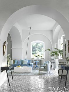 25 Rooms With Wonderful White Walls | Antique Italian mirrors hang above consoles by Conde House in the living room of this Capri home; the slipper chairs are by Creazioni, and the antique tile flooring is original to the house.