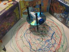 """""""Doodlebot"""" made with a dollar store electric toothbrush, an old CD or DVD, and three markers. Imagination at work!"""