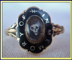Antique Georgian 18 carat gold and enamel Memorial, hair and skull ring. Made circa 1820.  Shank of the ring in the form of overlapping branches that divide into 3 at each shoulder, where they join the oval, flower-shaped bezel. Top has an oval reserve in which a skull rests on a bed of the beloved's tightly woven hair. The border is enamelled in black with gold letters: IN MEMORY OF.