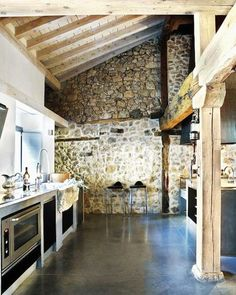 high vaulted ceiling, enforced with wooden planks and beams, inside a large kitchen, with dark smooth floor, modern appliances and stone-covered wall Rustic Kitchen Design, Dining Room Design, Home Decor Kitchen, Kitchen Dining, Kitchen Stone Wall, Barn Kitchen, Kitchen Designs, Country Kitchen, Home Interior